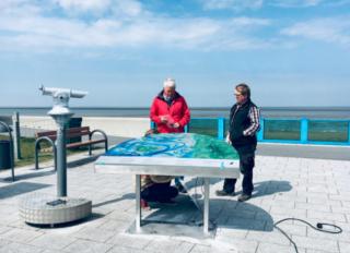 Die Infokarte mit Fernglas vor dem blauen Meer und Himmel