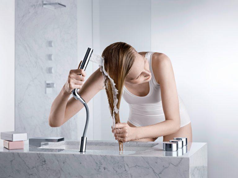 Eine Frau wäscht sich die Haare mit einer Handbrause