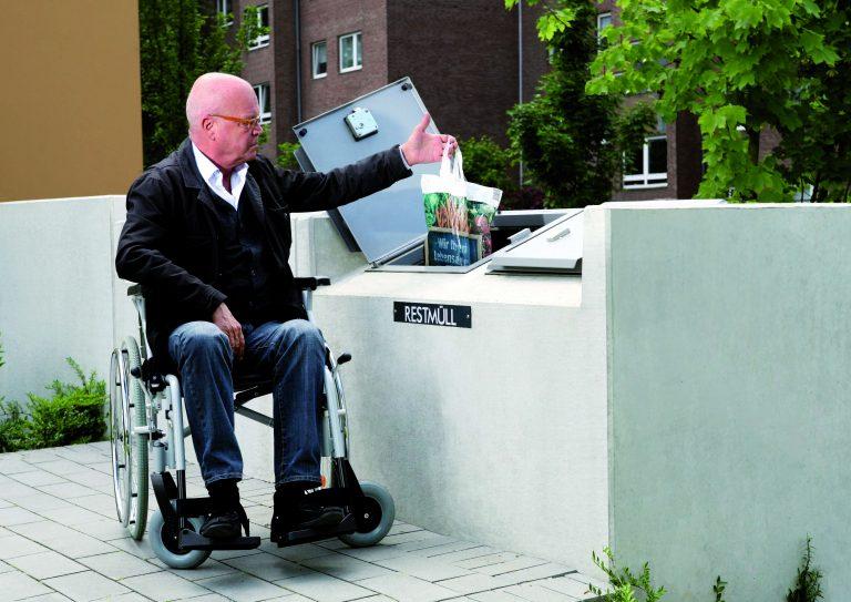 Ein Rollstuhlfahrer wirft in die niedrige Öffnung Müll in den Container