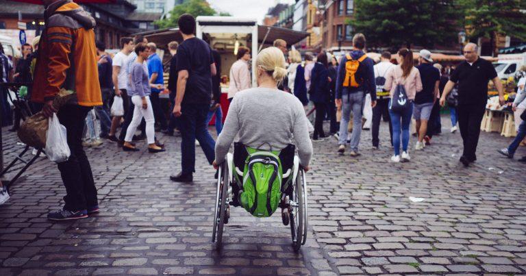 Rollstuhlfahrerin auf dem Pflaster des Hamburger Fischmarktes