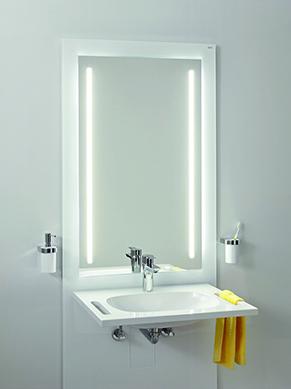 Das Bild zeigt einen im Vorwandsystem angebrahcten Waschtisch mit Spiegel. Das durchgängig gestaltete System ermöglicht gleichermaßen die Höhenverstellung von Waschtischen und WC-Becken – ein Vorteil für Nutzer verschiedenster Generationen und Körpergröße. Es fügt sich gut in die Badgestaltung ein und stellt die Funktionalität der Verstellbarkeit nicht in den Vordergrund. Die Integration eines beleuchteten Spiegels mit verschiedenen Farbtemperaturen ist ein weiterer Mehrwert.