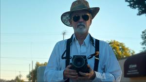 Der Künstler Pete Eckert mit seiner Mittelformatkamera vor blauem Himmel, er trägt Sonnenbrille und Hut
