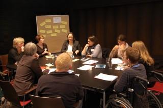 Workshop Runde mit Teilnehmern am Tisch